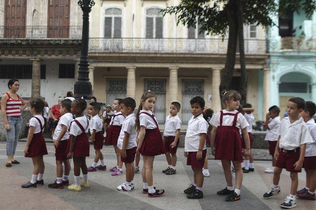 Kayla Hernandez, 5 (C), looks on school activities in downtown Havana January 20, 2015. (Photo by Alexandre Meneghini/Reuters)