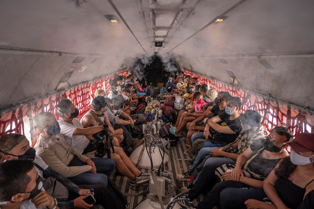 Residents of Providencia sit in a Colombia army plane with their belongings as they are being evacuated on November 21, 2020 in Providencia Island, Colombia. The islands of San Andres, Providencia and Santa Catalina were hit by Hurricane Iota in the early hours of Monday 16th as a category 5 storm, the strongest to affect the country since records are kept. The islands' economy depends on the tourism industry which has been suffering due to coronavirus restrictions since March. According to official sources, 98% of the Providencia Island infrastructure was destroyed by Iota's winds. President Duque, now visiting San Andres Island, contacted the US government for humanitarian help and assistance in hurricane crisis management. (Photo by Diego Cuevas/Getty Images)