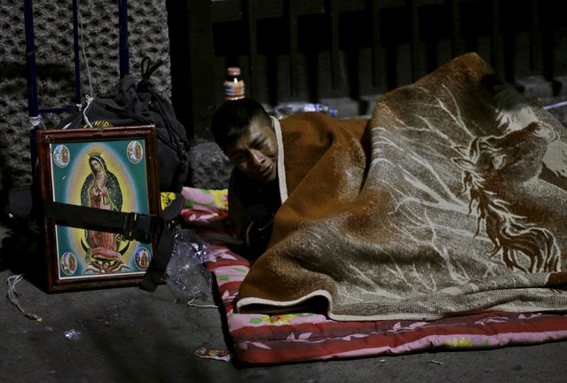 A pilgrim rests beside an image of the Virgin of Guadalupe next to an improvised camp site outside the Basilica of Guadalupe during the annual pilgrimage in honor of the Virgin of Guadalupe, patron saint of Mexican Catholics, in Mexico City, Mexico December 11, 2015. (Photo by Henry Romero/Reuters)