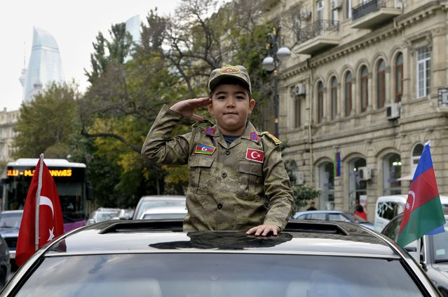 A boy wearing the Azerbaijan's military uniform salutes during celebrations in the streets of the capital Baku on November 10, 2020, after Armenia and Azerbaijan agreed a ceasefire following a string of Azeri victories in fighting over the disputed Nagorno-Karabakh region. Armenia and Azerbaijan agreed on a deal with Russia to end weeks of fierce clashes over Nagorno-Karabakh on November 10, 2020, after a string of Azerbaijani victories in its fight to retake the disputed region. (Photo by Tofik Babayev/AFP Photo)