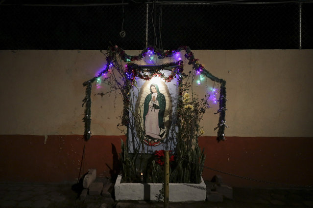 A neighborhood shrine to the Virgin of Guadalupe built in a wall is seen in Mexico City, Friday December 11, 2020. Nationwide, devotees of the Virgin make a pilgrimage to the Basilica in honor of her December 12 feast day, but the Catholic Church announced the closure of the Basilica for this year's pilgrimage due to the coronavirus pandemic. (Photo by Eduardo Verdugo/AP Photo)