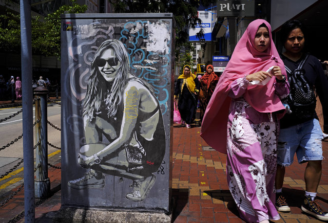 In this Sunday, June 17, 2018, file photo, an Indonesian resident walks past graffiti on a downtown street in Hong Kong. There are 370,000 foreign domestic helpers in the Chinese territory and about 49.4 percent from Indonesia. (Photo by Vincent Yu/AP Photo)