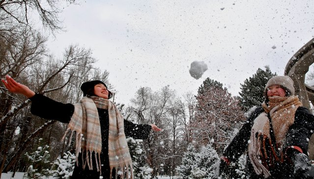 People frolic in a park after a snowfall in Bishkek, Kyrgyzstan, 25 February 2021. Reports state that the air temperature in Bishkek has fallen to -12 degrees Celsius. (Photo by Igor Kovalenko/EPA/EFE)