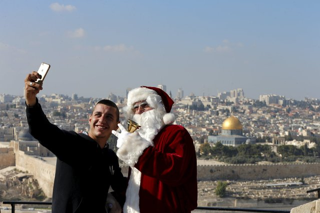 A Palestinian man takes a selfie with Israeli-Arab Issa Kassissieh as he wears a Santa Claus costume during an annual Christmas tree distribution by the Jerusalem municipality on the Mount of Olives in Jerusalem December 21, 2015. The Dome of the Rock is seen in the background. (Photo by Ammar Awad/Reuters)