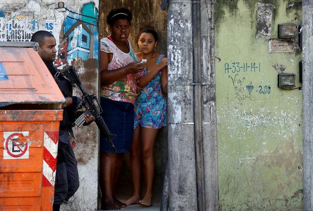 A policeman takes position during an operation against drug dealers in Cidade de Deus or City of God slum in Rio de Janeiro, Brazil, November 20, 2016. (Photo by Ricardo Moraes/Reuters)