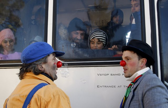 Members of Red Noses Clowndoctors entertain migrants before their departure to Austria at a registration center in Dobova, Slovenia, December 27, 2015. (Photo by Srdjan Zivulovic/Reuters)