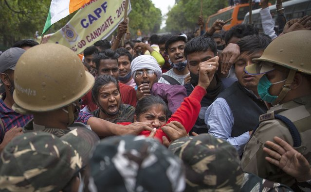 Members of National Students Union of India (NSUI), the student body of the Congress party, scuffle with Indian paramilitary soldiers as they protest against rising unemployment in New Delhi, India, Friday, March 12, 2021. (Photo by Altaf Qadri/AP Photo)