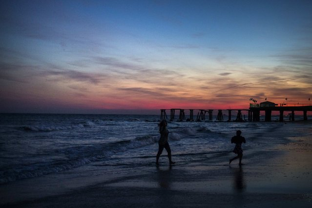Family members are silhouetted along the beachfront during sunset in Atlantic City, New Jersey September 12, 2014. (Photo by Adrees Latif/Reuters)