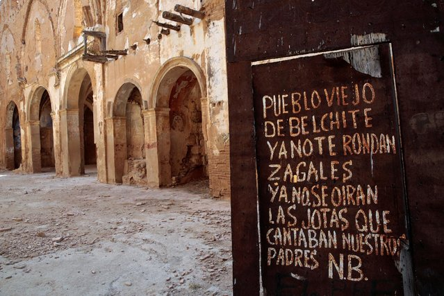 """A graffiti is seen on the entrance door of San Martin de Tours church in the old village of Belchite, in northern Spain, October 3, 2016. The graffiti reads: """"Old town of Belchite, young men don't wander around you anymore. The jots (typical songs and dance of the area) that our fathers used to sing, won't be heard anymore"""". (Photo by Andrea Comas/Reuters)"""