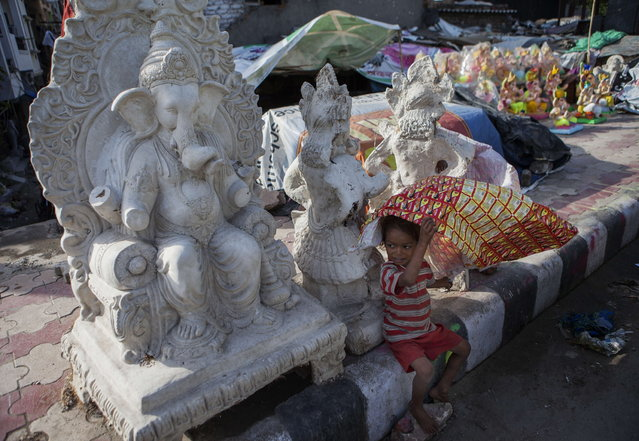 An Indian child plays in front of Ganesh statues  being sold near the road ahead of the Ganesh Chaturthi festival in New Delhi on September 2, 2013. The Hindu festival which celebrates the rebirth of the God Lord Ganesha, starts September 9 and culminates on September 19, with many of the statues being immersed in bodies of water. (Photo by Andrew Caballero-Reynolds/AFP Photo)