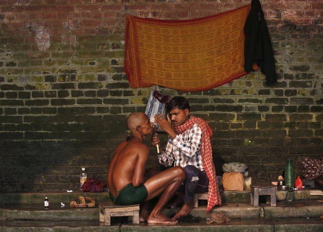A Hindu man has his head shaved by a barber on the banks of the Ganges river, as part of a Hindu ritual after his mother died, in Kolkata, India, December 29, 2015. Many Hindus come to the banks to have their heads shaved, perform prayers and take a dip in the waters as part of the final rites for the deceased. (Photo by Rupak De Chowdhuri/Reuters)