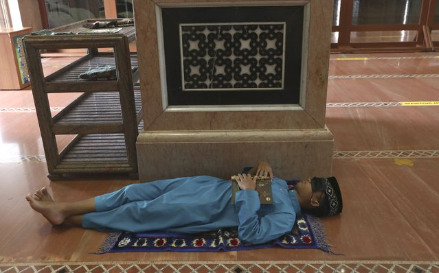 A man takes a nap while waiting for the time to break his fast at the Kubah Mas mosque in Depok, Indonesia, Friday, April 16, 2021. (Photo by Tatan Syuflana/AP Photo)