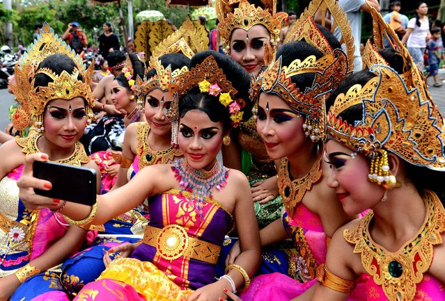 Balinese young girl take a selfie during a New Year celebration in Denpasar, on Indonesia's resort island of Bali on December 31, 2015. Various form of dances and music have made Bali's art and culture one of the most diverse in the world. (Photo by Sonny Tumbelaka/AFP Photo)