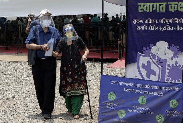 People wearing face shields and masks as a precaution against the coronavirus arrive to receive COVID-19 vaccine in Mumbai, India, Thursday, April 29, 2021. India set another global record in new virus cases Thursday, as millions of people in one state cast votes despite rising infections and the country geared up to open its vaccination rollout to all adults amid snags. (Photo by Rajanish Kakade/AP Photo)
