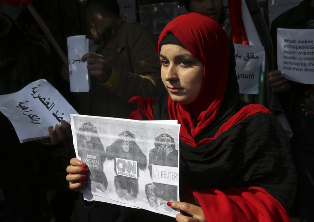 A Palestinian woman holds a poster during a protest organized by the Palestinian Youths Organization against three young Muslim students who were shot dead by their neighbor in North Carolina last week, in Gaza City, in the northern Gaza Strip, Monday, February 16, 2015. (Photo by Adel Hana/AP Photo)