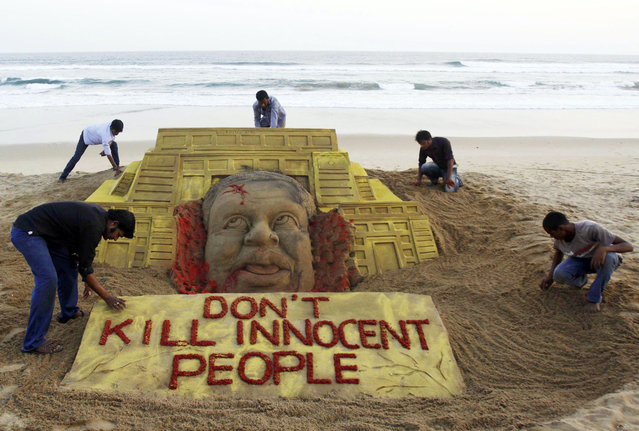 Indian sand artist Sudarshan Pattnaik, foreground left and his team pay tributes to the victims of the terror attack on a Kenya mall by creating a sand sculpture on the Bay of Bengal coast in Puri, Orissa state, India, Tuesday, September 24, 2013. (Photo by Biswaranjan Rout/AP Photo)
