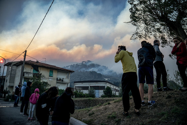 Inhabitants look at the fire on the nearby hills in Calci, near Pisa in Tuscany region, on 25 September 2018. A very extended fire is burning the hills north of the town of Pisa. Hundreds had to leave their home during the night. Vigili del fuoco, Italian fire brigades, and volunteers work to stop the fire, close to many populated areas. (Photo by Federico Scoppa/AFP Photo)