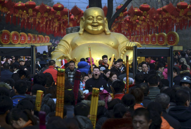In this Thursday, February 19, 2015 photo, a security guard, center, yawns as visitors crowd the entrance of Badachu Temple during the temple fair for a Lunar New Year celebration in Beijing. (Photo by AP Photo)