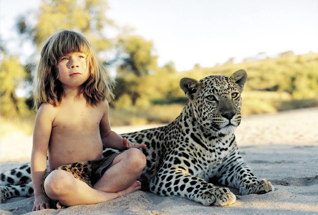 Tippi aged 6 sitting with J&B, a tame adult leopard in Namibia, 1996. (Photo by Sylvie Robert/Barcroft Media)