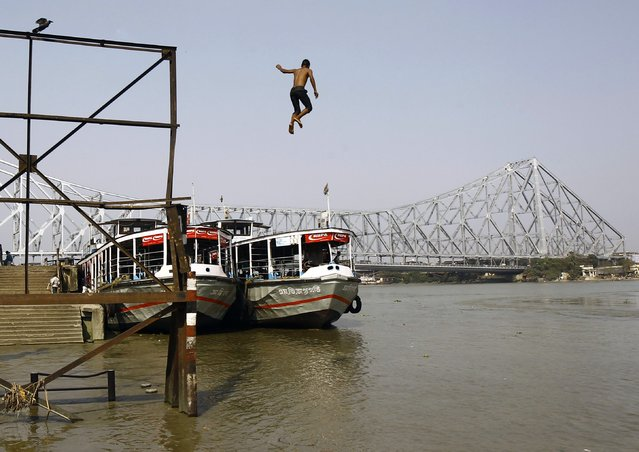 A boy jumps into the river Ganges to swim in Kolkata, India February 23, 2015. (Photo by Rupak De Chowdhuri/Reuters)