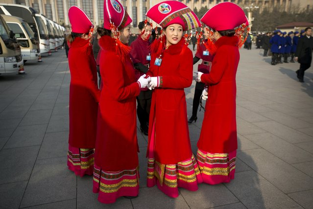 Hostesses gather outside the Great Hall of the People during the opening session of the annual National People's Congress in Beijing, Thursday, March 5, 2015.China announced a lower economic growth target for this year and promised to open more industries to foreign investors as it tries to make its slowing, state-dominated economy more productive. (AP Photo/Mark Schiefelbein)