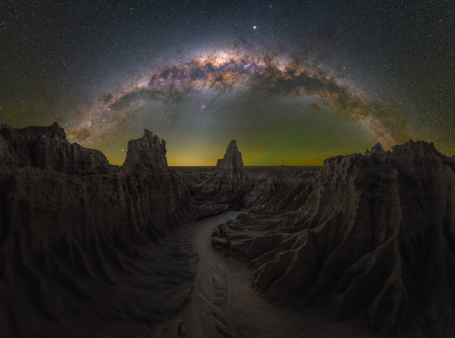 """Dragon's lair; Mungo, NSW, Australia. """"This is my favourite nightscape image to date. Mungo is a 12-hour drive away from my home in Sydney, but those Bortle 1 skies are the best I've ever witnessed and photographed at night. I had perfect conditions for three straight nights, with really good seeing throughout. The moment I came upon this scene, I knew exactly what I wanted to the name the image. It was otherworldly – think Game of Thrones – and it lined up perfectly for how I wanted to capture it. Large, jagged walls framed a winding path leading to a centred spire to the west. There was only ever going to be one way to do it justice and that was as a multi-layered Milky Way panorama. I planned this image using PhotoPills during the day, but in post-processing, I decided to use the blue-hour blend for the foreground with a tracked sky for the cleanest possible image"""". (Photo by Daniel Thomas Gum/Milky Way Photographer of the Year)"""
