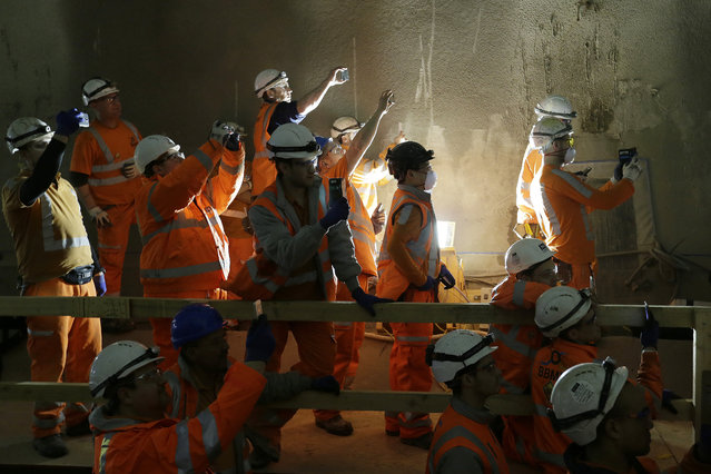Workers watch and take pictures as tunnel boring machine Victoria break into the eastern end of the Liverpool Street Crossrail station in London, Tuesday, March 10, 2015. Liverpool Street is one of 10 new Crossrail stations being built in central and southeast London, part of the capital's new railway line due to be fully operational in 2019. (AP Photo/Tim Ireland)