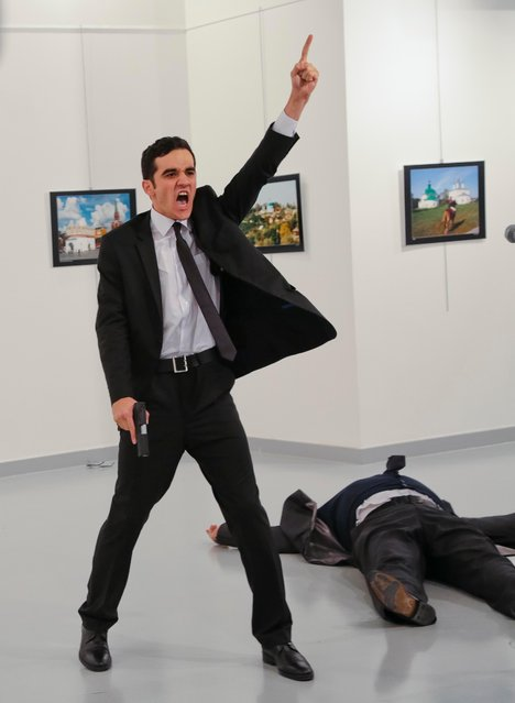"A man identified as Mevlut Mert Altintas shouts after shooting Andrei Karlov, the Russian Ambassador to Turkey, at a photo gallery in Ankara, Turkey, Monday, December 19, 2016. Shouting ""Don't forget Aleppo! Don't forget Syria!"" Altintas fatally shot Karlov in front of stunned onlookers at a photo exhibit. (Photo by Burhan Ozbilici/AP Photo)"