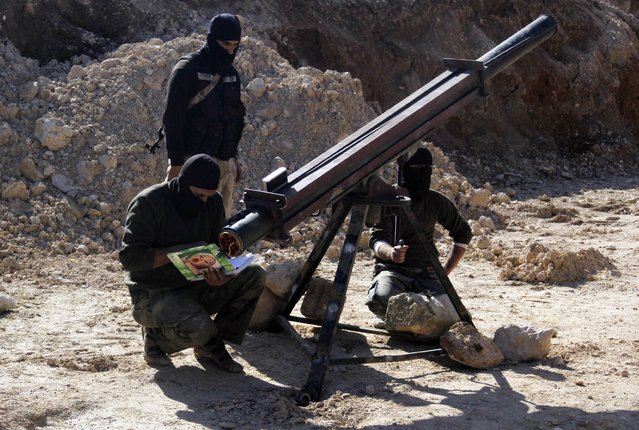 Rebel fighters prepare Grad rockets to be launched toward forces of Syria's President Bashar al-Assad stationed in al-Suqaylabiyah district, from the orchards north of Kfar Zeita village in the northern countryside of Hama January 29, 2015. (Photo by Mohamad Bayoush/Reuters)