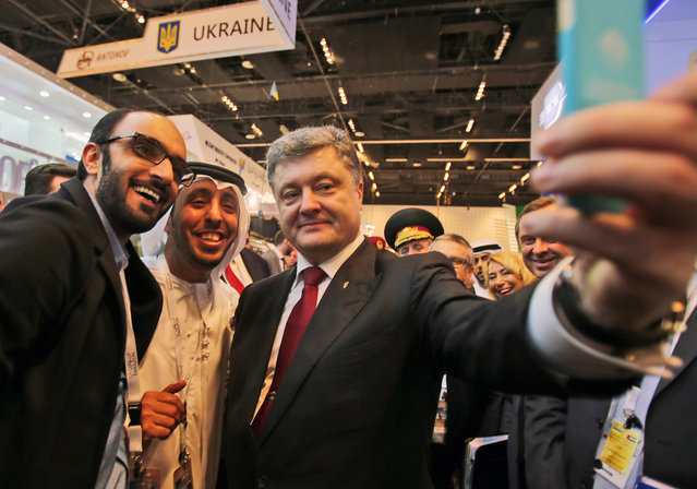 Ukrainian President Petro Poroshenko takes a selfie with an Emirati media representative at the International Defence Exhibition and Conference, IDEX, in Abu Dhabi, United Arab Emirates, Tuesday, February 24, 2015. (Photo by Kamran Jebreili/AP Photo)