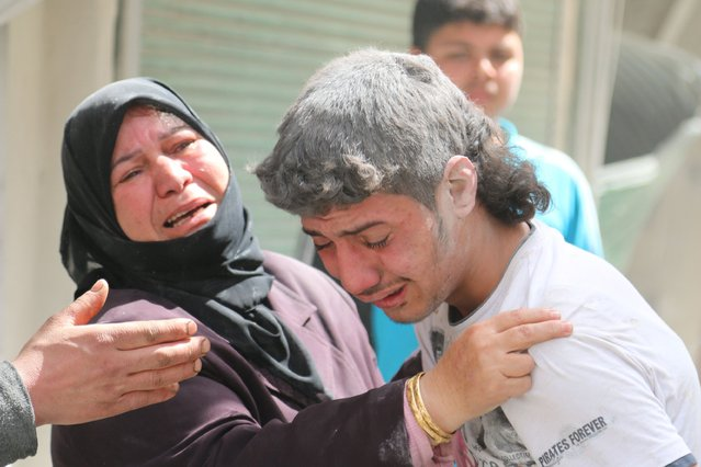 A mother and her son mourn the loss of their relatives caused by what activists say was a barrel bomb dropped by forces loyal to Syria's President Bashar al-Assad, in Aleppo's al-Fardous district April 29, 2015. (Photo by Mahmoud Hebbo/Reuters)