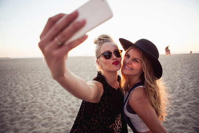 Female friends photographing themselves on smartphone. (Photo by Christin Rose/Cultura RM Exclusive/Getty Images)