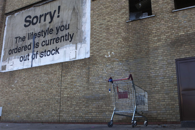 A new work by Banksy, in the form of a billboard, adorns a wall near the Canary Wharf financial district in London, December 22, 2011. (Photo by Finbarr O'Reilly/Reuters)