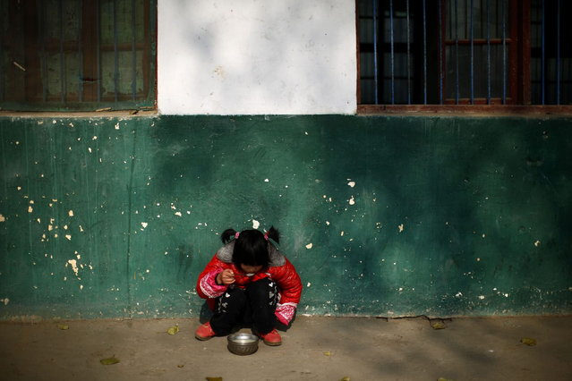 A student eats lunch as she sits on the ground at the Democracy Elementary and Middle School in Sitong town, Henan province December 4, 2013. (Photo by Carlos Barria/Reuters)