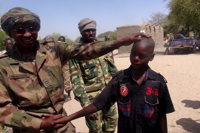A Chadian soldier embraces a former child soldier of insurgent group Boko Haram in Ngouboua, Chad, April 22, 2015. The young men said they were Chadian nationals forced to join Boko Haram while studying the Koran in Nigeria, and that they escaped and turned themselves in to Chadian authorities. (Photo by Moumine Ngarmbassa/Reuters)