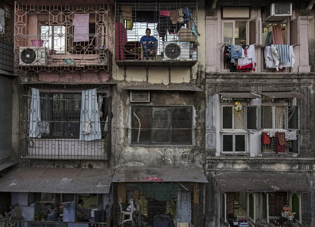 A resident sits on a balcony of an apartment in Mumbai March 15, 2015. The cost for buying a 200 square feet (18 square meters) one-bedroom apartment in this building is around 25,000 Indian rupees per square feet ($ 400) or 5,000,000 Indian rupees ( $80,000). The rent for an apartment in the same building is around 12,000 Indian rupees ($ 190) per month. (Photo by Danish Siddiqui/Reuters)
