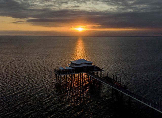 The sun rises behind the pier over the Baltic Sea in Timmendorfer Strand, Germany, early Tuesday, July 20, 2021. (Photo by Michael Probst/AP Photo)