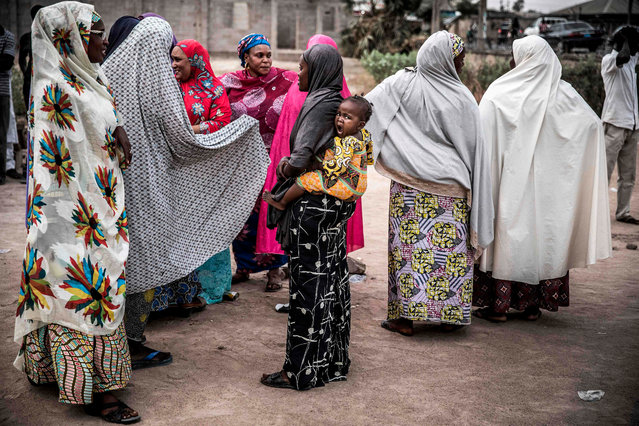 A girl yawns when carried by her mother when some women gather together during the closing of their polling unit at Shagari Health Unit polling station in Yola, Adamawa State on February 23, 2019 after the polls were closed during the day of the General elections. (Photo by Luis Tato/AFP Photo)