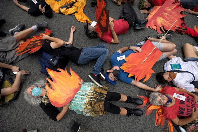 """People block a street in Manhattan while pretending to be dead during a """"non-violent resistance"""" climate change protest organized by Extinction Rebellion in the Manhattan borough of New York City, U.S., September 17, 2021. (Photo by Caitlin Ochs/Reuters)"""
