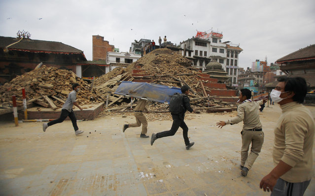 Volunteers run with a stretcher to carry a dead body recovered from the debris of a building that collapsed after an earthquake  in Kathmandu, Nepal, Saturday, April 25, 2015. (Photo by Niranjan Shrestha/AP Photo)