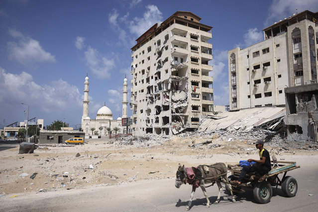 A Palestinian man rides his donkey cart past a building that was destroyed during the recent 11-day war between Israel and the Palestinian Hamas movement, in Gaza City, on September 23, 2021. (Photo by Mohammed Abed/AFP Photo)