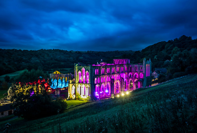 The remains of the 11-century abbey is bathed in coloured light before Illuminating Rievaulx, North Yorkshire, UK a three-night light and sound installation. (Photo by Danny Lawson/PA Wire)