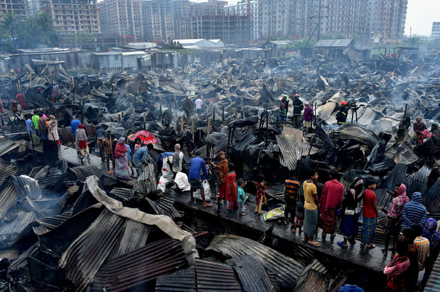 Residents inspect the scene after a fire destroyed 150 homes in a slum in Dhaka, Bangladesh on February 28, 2019. Two children were killed as the fire engulfed the area. (Photo by Xinhua News Agency/Barcroft Images)