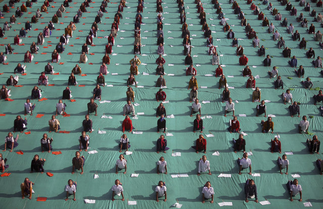 Schoolchildren attend a yoga session during a camp in the western Indian city of Ahmedabad, India, January 9, 2012. (Photo by Amit Dave/Reuters)