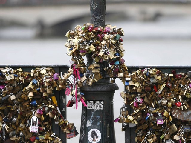 The love padlocks, called cadenas d'amour, multiplied until there were thousands of love tokens on the bridge, each engraved with a message of love. (Photo by Charles Platiau/Reuters)