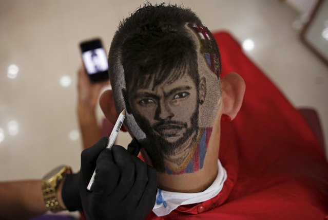 Hair artist and barber Nariko, 27, etches an image of Barcelona's Neymar on the head of customer Luiz Fernadez, 15, before the Champions League semifinal first leg soccer match between Barcelona and Bayern Munich, at his barbershop in Sao Vicente, near Santos, in Sao Paulo state May 6, 2015. (Photo by Nacho Doce/Reuters)