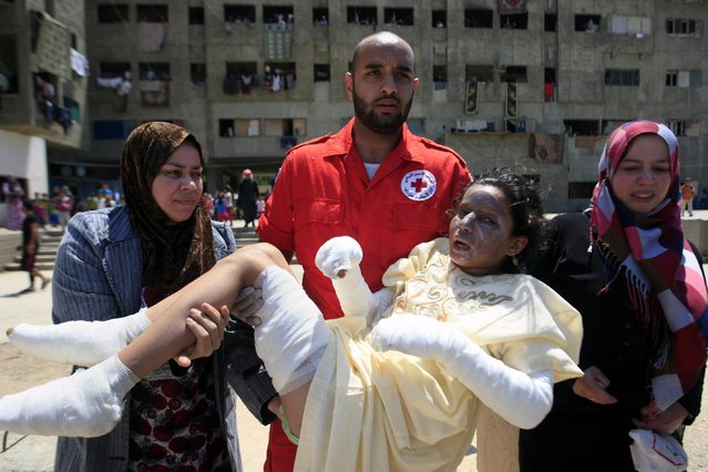 A Lebanese Red Cross volunteer carries Syrian refugee Shirin Salloum, 11, after suffering burns from fire caused by electricity short circuit in her building in the southern port city of Sidon, Lebanon, Thursday, May 7, 2015. The building is in a compound housing more than 500 Syrian refugees. (Photo by Mohammed Zaatari/AP Photo)
