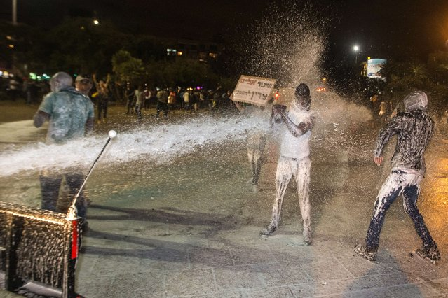 Israeli police uses water cannon during heavy clashes, to disperse Ethiopian Israelis demonstrating in central Tel Aviv against alleged police brutality May 3, 2015. The protest came three days after a stormy demonstration in Jerusalem sparked by footage showing two police officers beating an Israeli soldier of Ethiopian origin in uniform. More than 135,000 Ethiopian Jews live in Israel, having immigrated to the Jewish state in two waves in 1984 and 1991. (Photo by Jack Guez/AFP Photo)