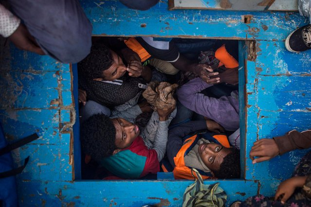A handout photo made available by the World Press Photo (WPP) organization on 13 February 2017 shows a picture by British photographer Mathieu Willcocks that won the Spot News – Third Prize, Stories award of the 60th annual World Press Photo Contest, it was announced by the WPP Foundation in Amsterdam, The Netherlands on 13 February 2017. Caption: Eritrean migrants seen cramped in the hold of a large wooden boat which carried approximately 540 men, women, and children. Story: The central Mediterranean migration route, between the coasts of Libya and Italy, remains busy. According to reports by the UNHCR, 5,000 people died while attempting to cross the Mediterranean in 2016. NGOs and charities such as Migrant Offshore Aid Station (MOAS) continue their efforts to patrol the patch of sea north of the Libyan coast, in the hope of rescuing refugees before the potential of drowning. The rescue team on board the MOAS' Responder are there to mitigate loss of life at sea. Operating like a sea-born ambulance, they rush to assist and rescue refugee vessels in distress, provide medical assistance, and bring the refugees safely to Italy. (Photo by Mathieu Willcocks/EPA/World Press Photo)