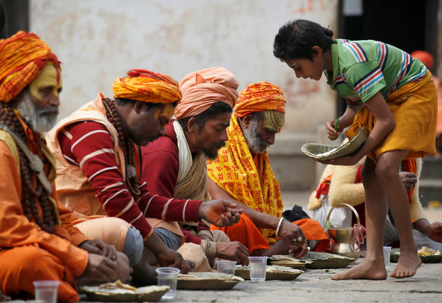 Hindu holy men, or sadhus, are offered lunch at the premises of Pashupatinath Temple, ahead of the Shivaratri festival in Kathmandu, Nepal February 15, 2017. (Photo by Navesh Chitrakar/Reuters)